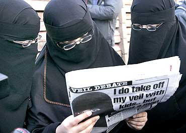 Muslim women read a newspaper article in London