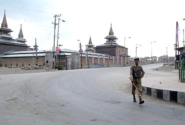 A security personnel walks through the deserted streets of Srinagar as curfew was clamped in few parts of the city on Tuesday