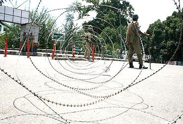 Police patrol behind concertina wire near martyrs' graveyard in Srinagar