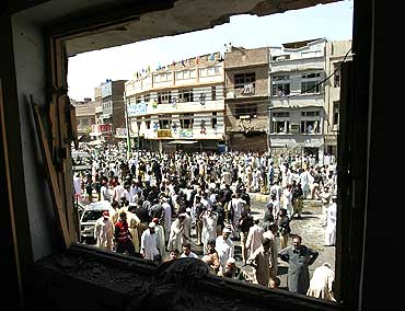 Pakistanis gather at the site of a bomb blast in Peshawar