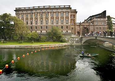 A fisherman lifts his net from a canal next to Sweden's Riksdagshuset, or Parliament building, in Stockholm