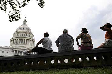 Tourists sit in the shade near the US Capitol in Washington
