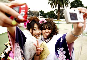 Japanese women take pictures of themselves at Toshimaen amusement park in Tokyo