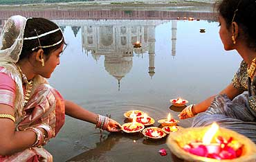 Teenagers place oil lamps on the Yamuna river behind the Taj Mahal