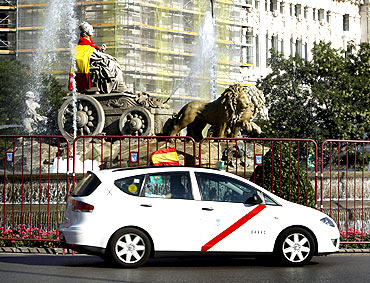 A taxi with a Spanish flag drives past the Cibeles statue wrapped in another flag in Madrid, July 9
