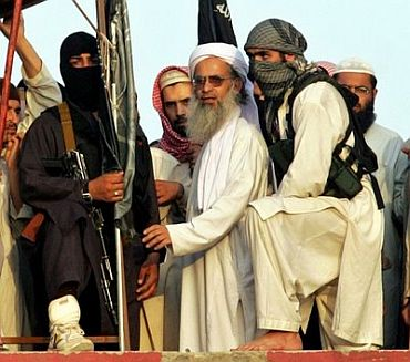 File photo dated March 8, 2007, shows radical Pakistani cleric Abdul Aziz (2-R) surrounded by guards as he stands on a roof of the Lal Masjid or Red Mosque during a protest in Islamabad