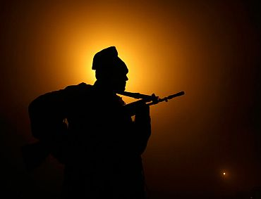 A paramilitary trooper patrols near the fencing at the India-Pakistan border at Suchetgarh, 30km south of Jammu