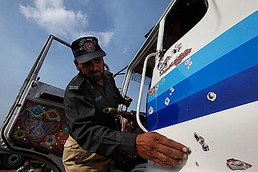 A policeman inspects a bullet riddled truck, which was carrying supplies to Kabul, after it was attacked while leaving Karachi for Kandahar