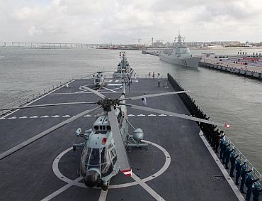 A Chinese Navy helicopter is parked on a warship on part call