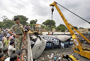 A crane lifts a damaged carriage of a passenger train at the site of accident at Sainthia on Monday