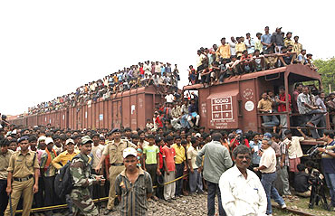 Onlookers stand on top of a goods train at the accident site