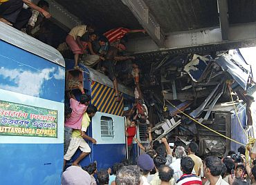 Volunteers conduct rescue operations on the wreckage of train carriages at Sainthia