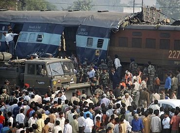Onlookers stand at the site of a train accident on the outskirts of Mathura