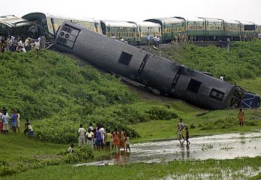 Onlookers and railway officials stand beside derailed carriages of a passenger train after an explosion in Kokrajhar