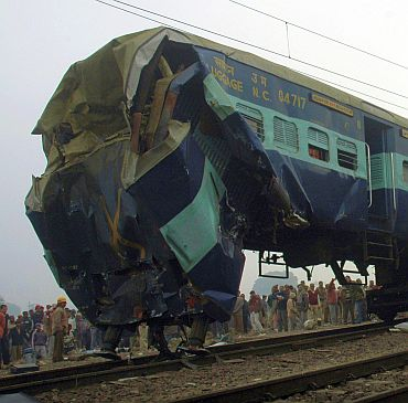 Onlookers gather near the damaged wreckage of a train carriage at the site of an accident at Gola village, on the outskirts of Tundla Railway Station, east of Agra