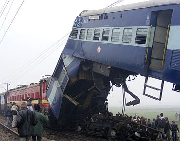 Onlookers gather around the wreckage of a train at the site of an accident in Etawah
