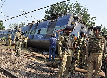Police and railway officials stand next to an overturned coach of the passenger train