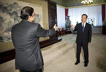 Pakistan President Asif Ali Zardari and China's Premier Wen Jiabao extend their hands out to each other during their meeting at Zhongnanhai in Beijing, July 8, 2010