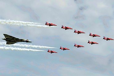The Royal Air Force Red Arrow display team and a Vulcan aircraft fly over the 2010 Farnborough International Airshow in Farnborough, southern England