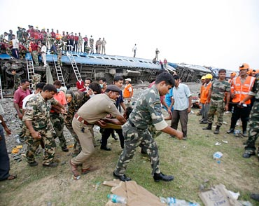 Army personnel carry an injured passenger at the site of the train mishap near Jhargram in May