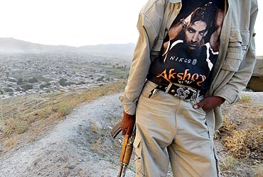 An armed Afghan man sports a photograph of Akshay Kumar on his t-shirt