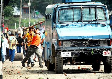 Protestors vandalise a police van in Srinagar