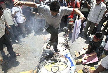 A man jumps on a burning effigy of General Than Shwe during a protest in New Delhi