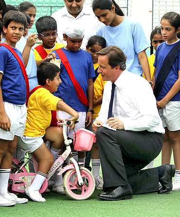 Britain's Prime Minister David Cameron signs autographs for children inside a stadium in New Delhi on Thursday
