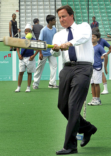 David Cameron plays cricket inside a stadium in New Delhi on Thursday