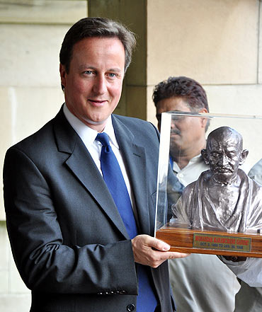 Cameron holds a bust of Mahatma Gandhi at Rajghat in New Delhi on Thursday