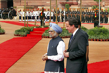 Cameron and Indian PM Manmohan Singh walk during Cameron's ceremonial reception on Thursday