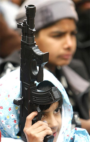 A supporter of the Jamaat-e-Islami holds a toy gun at an anti-India rally