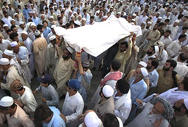 Residents carry the draped body of a suicide bomb victim to his grave in Pabbi, Peshawar