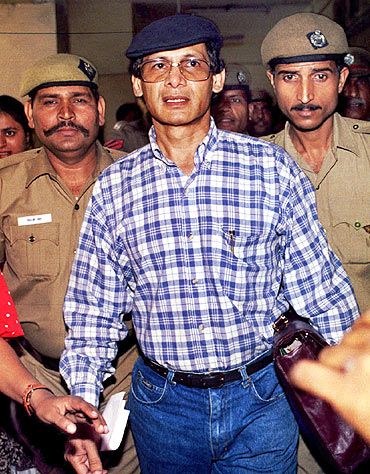 Indian policemen escort Charles Sobhraj as he leaves a New Delhi court in 1995