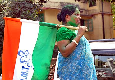 A woman supporter holds a Trinamool flag