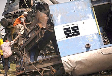 Rescuers work at an overturned carriage of a crashed train at Jhargram. Indian police began searching for Maoists rebels believed responsible for sabotaging the train
