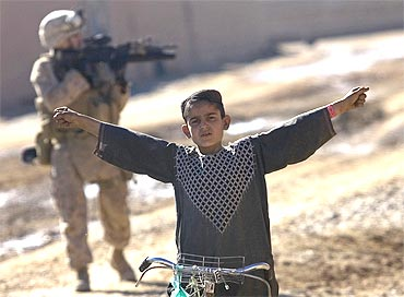 An Afghan boy gestures as US Marine from India Company, patrol in the town of Delaram in southern Afghanistan