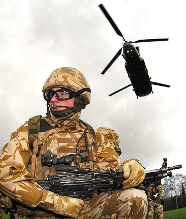 A soldier from the 1st Royal Welsh batallion waits for a chinook helicopter to land.