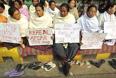 Women hold placards during a protest against the Armed Forces Special Powers Act