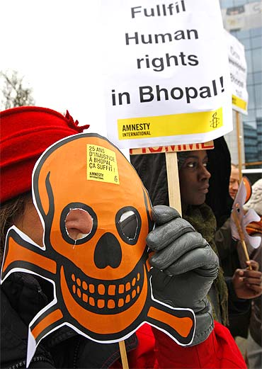 Activists of Amnesty International wear masks representing victims of the Bhopal gas tragedy