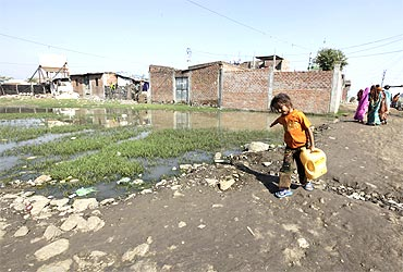 A girl carries water in a slum area next to the Union Carbide Corp pesticide plant in Bhopal