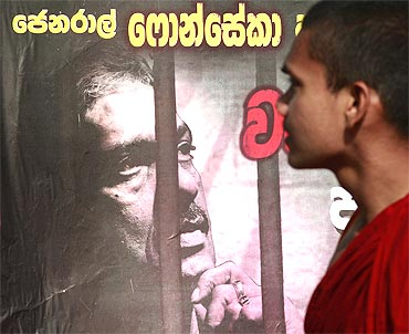 A Buddhist monk walks past a poster of defeated presidential candidate General Sarath Fonseka before the start of a rally against Fonseka's arrest in Colombo on March 8, 2010