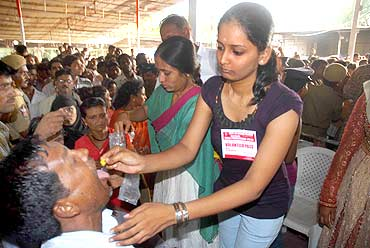 A volunteer distributes fish Prasadam at a camp in Hyderabad