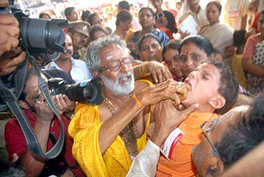 A child being given the fish prasadam