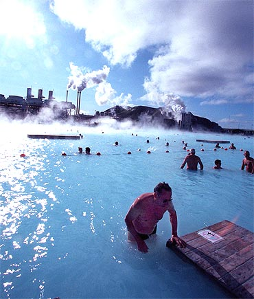 Bathers at the Blue Lagoon hot springs swim in hot mineral waters amid a chilly wind
