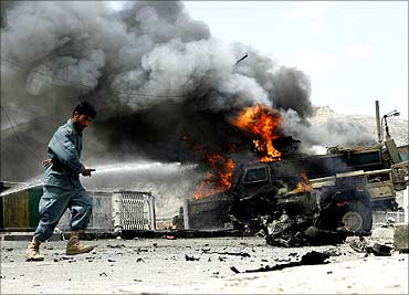 An Afghan policeman walks in front of a burning US armoured vehicle which was hit by a suicide bomber in Nangahar province