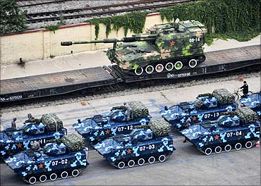Military vehicles wait in a line in Beijing