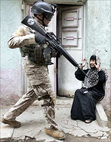 An Iraqi soldier passes a woman during a military operation in Baghdad's al-Fadhil district