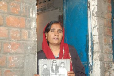 Shamshad Bi stands with a photograph of her family who died in the tragedy