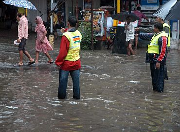 Municipal workers assist people wading through a water-logged street